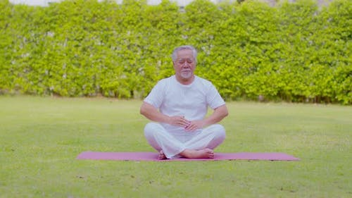 Calm of Healthy Senior Asian man wearing white shirt and pant doing Tai Chi Chuan for Meditation