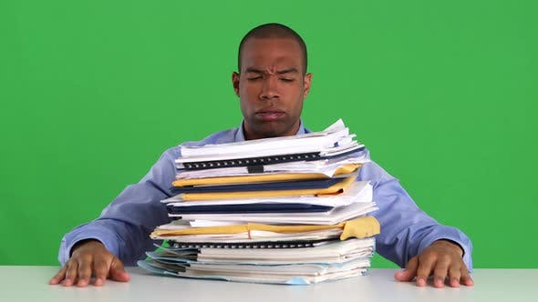 Thumbnail for Frustrated and overwhelmed businessman pushing pile of work off desk