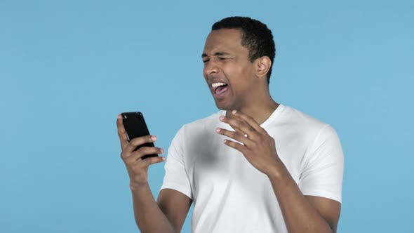 Thumbnail for Young African Man Reacting To Loss and Using Smartphone