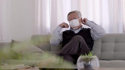 Asian elderly wear masks stay in living room.