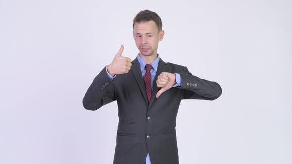 Thumbnail for Studio Shot of Businessman Choosing Between Thumbs Up and Thumbs Down
