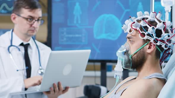 Doctor Using His Laptop in a Modern Facility for Brain Research