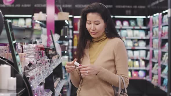 Asian Woman Shopping In Cosmetics Store