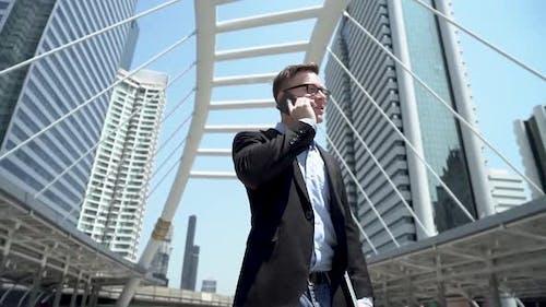 Businessman Talking On Phone At City