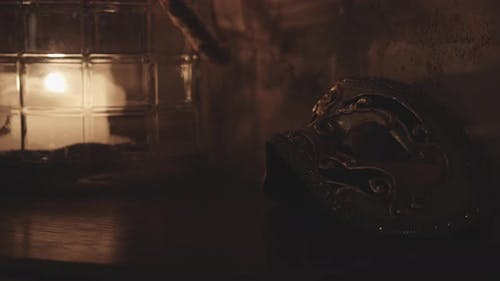 Metallic Gold Masquerade Mask Together With a Lit Candle Taken on a Steady Shot