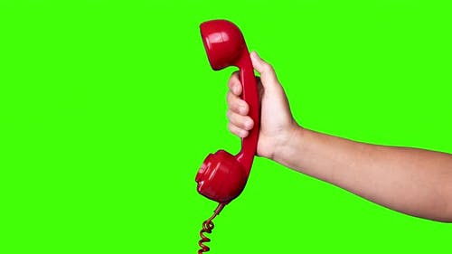 Hand Holding the Receiver of a Retro Red Telephone