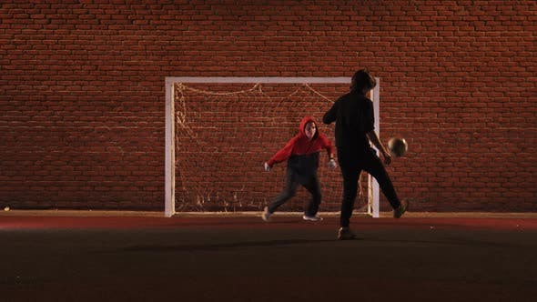 Thumbnail for Two Young Friends Playing Football on the Outdoor Playground at Night