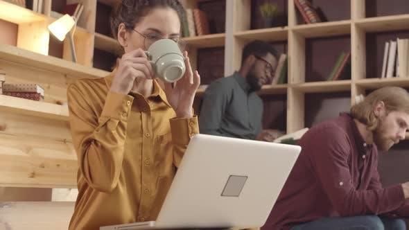 Thumbnail for Lächelnder kaukasischer Blogger mit Laptop trinken Kaffee im Hipster Cafe