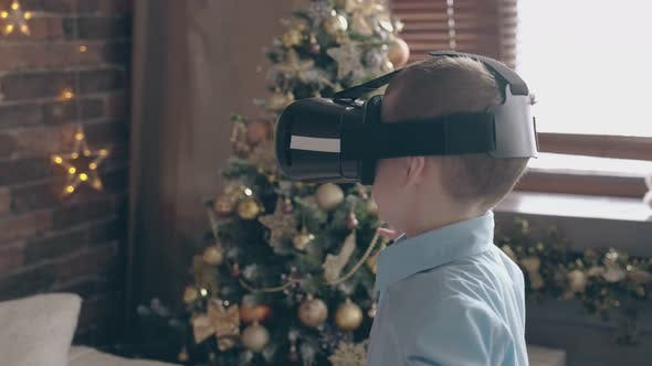 Adorable Boy Kid in Blue Shirt Plays with VR Headset