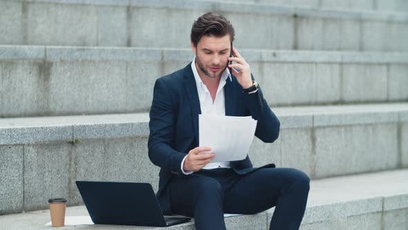 Thumbnail for Businessman Talking on Smartphone with Client. Executive Reading Business Papers