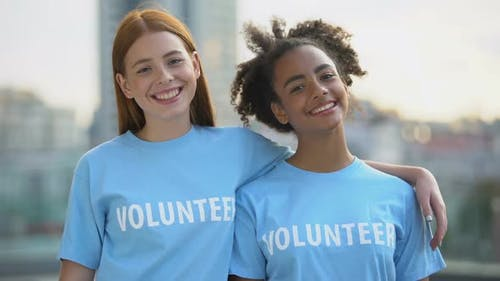 Two Female Volunteers Smiling on Camera, High School Charity Program, Altruism