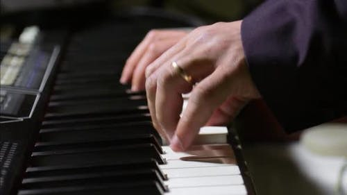 Musician playing on the keyboard synthesizer piano keys. Musician plays a musical instrument