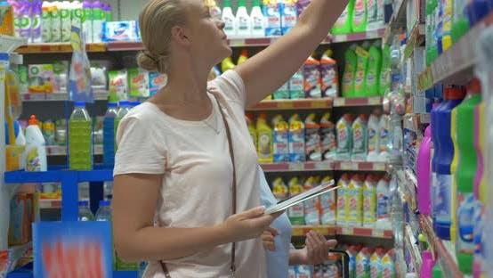 Women Choosing Household Detergents in the Supermarket