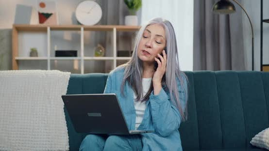 Woman with Grey Hair which Talking on Mobile and Working on Laptop