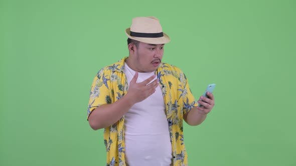 Thumbnail for Happy Young Overweight Asian Tourist Man Using Phone and Looking Surprised