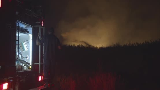 Fire Truck with Flashing Light on Background Burning Field.