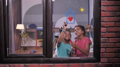 Smiling Dark-skinned Girls Painting on Window