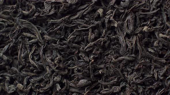 Thumbnail for Leaves of Black Tea Background, Close Up. Rotation. Front of the Camera Rotates Plate with Black Tea