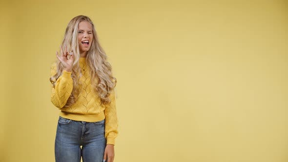 Cover Image for Attractive Lady Pointing to Her Right and Giving an Okay Sign