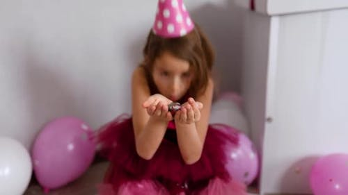 Beautiful little girl blows up multicolored confetti, having fun at home birthday party