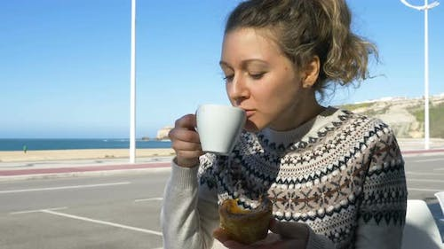 Pretty Girl Enjoys Drinking Tea and Eating Cake By Ocean