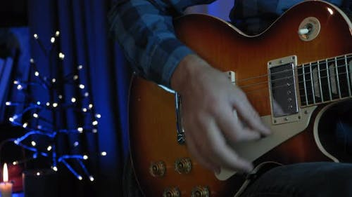 Professional musician is performing romantic lyric song on electric guitar at vocal rehearsal studio
