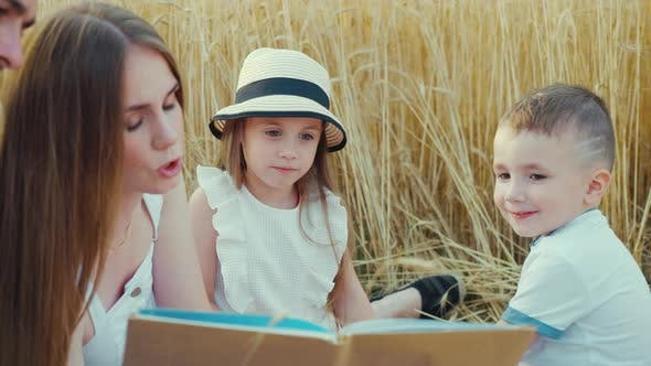 Mom Reading Book to Children at Family Picnic