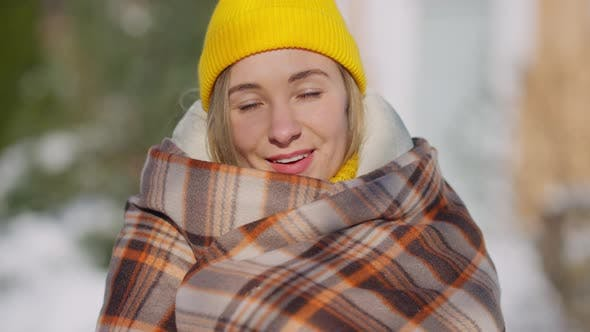 Headshot Portrait of Happy Young Woman in Yellow Hat Wrapping in Blanket Standing Outdoors Looking