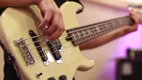 Close-up of Male Bassist Hands Playing on Electric Bass Guitar Touching Strings on Rehearsal