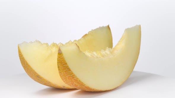 Melon slices rotating on white background