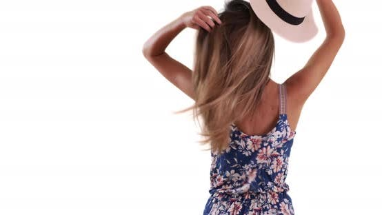 Thumbnail for Rear view of young lady taking off hat and letting hair flow on white backdrop