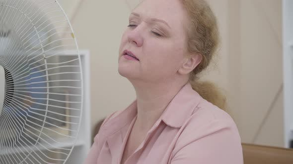 Close-up of Senior Woman Using Electric Fan Indoors. Portrait of Ill Caucasian Lady Having Fever or