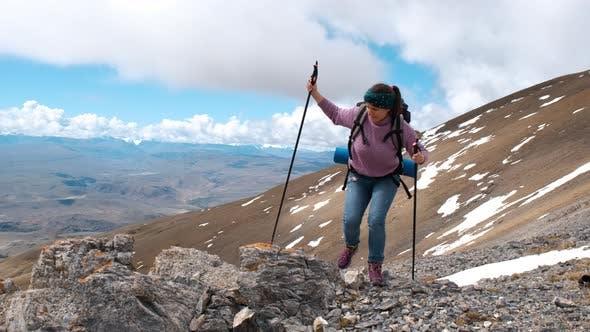 Woman Hiker Climbing on a Peak of a Mountain