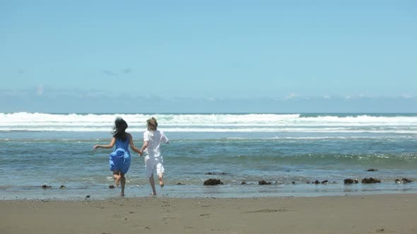 Thumbnail for Couple holding hands and running to ocean