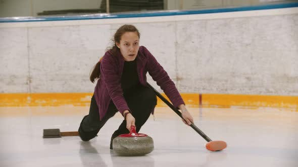 Thumbnail for Curling - a Woman in Glasses Skating on the Ice Field and Leading a Granite Stone To the Certain