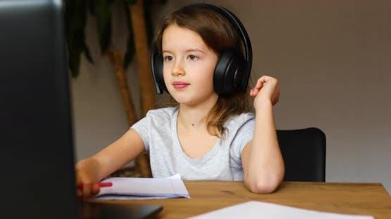 Nettes kleines Mädchen mit Kopfhörern mit Laptop, um zu Hause zu lernen