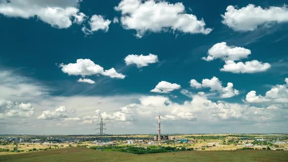 Cover Image for Industrial Landscape with Power Plant with Yellow Field and Big Blue Clouds. Timelapse