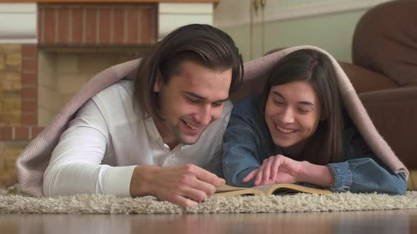 Thumbnail for Happy Young Guy and Girl Lying on the Carpet on the Floor and Reading a Book