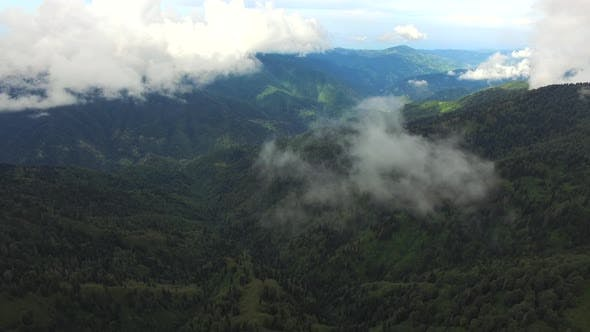 Flying Through the Cloud Parts Over the Vast Forested Mountains