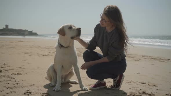 Thumbnail for Smiling Beautiful Lady in Eyeglasses Sitting on Sandy Beach with Pet