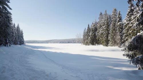 A Snowcovered Valley with a Footprint Trail
