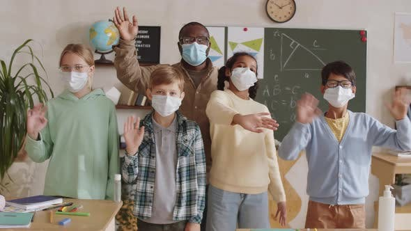 Thumbnail for Teacher and Pupils in Face Masks Waving at Camera in School Classroom