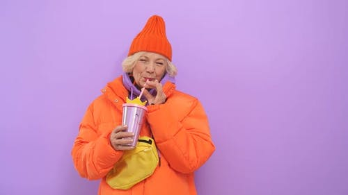 Close-up Portrait of an Attractive Older Woman Dressed in an Orange Hat and Jacket, She Poses for