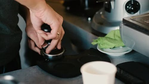 Process of making espresso in a coffee machine. Barista making latte in  specialty coffee shop.