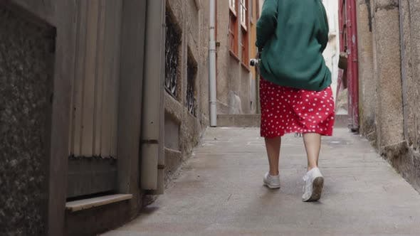 Thumbnail for Woman Is Running in Old Narrow Street Looking Back On Camera and Smiling