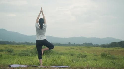 Beautiful Asian female doing yoga exercise meditation performing a spiritual yoga pose.