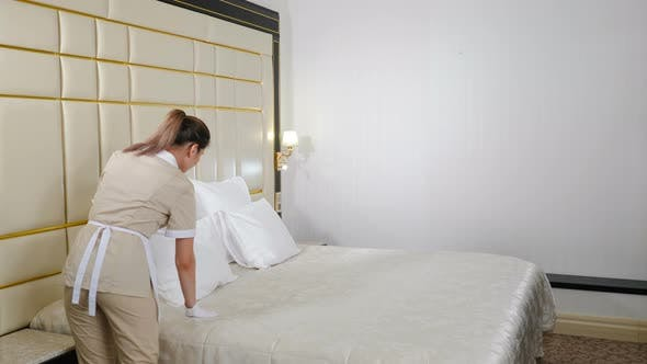Cleaning in Hotel. Pretty Maid in Uniform Touching Bed Cover with Gloved Hand Then Punching Pillow