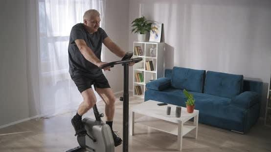Training mit stationärem Fahrrad in der Heimat Mann mittleren Alters ist Trainings- und Drehpedale, die sich fit halten