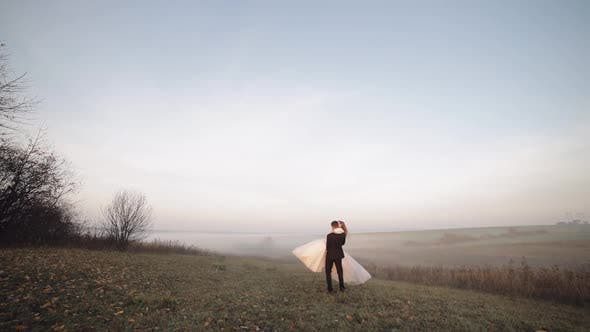 Thumbnail for Newlyweds Dancing. Caucasian Groom with Bride on the Morning Field. Fog. Wedding