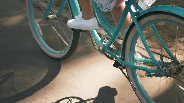 Thumbnail for Happy beautiful girl is spinning pedals on vintage bike. Woman legs riding a bicycle